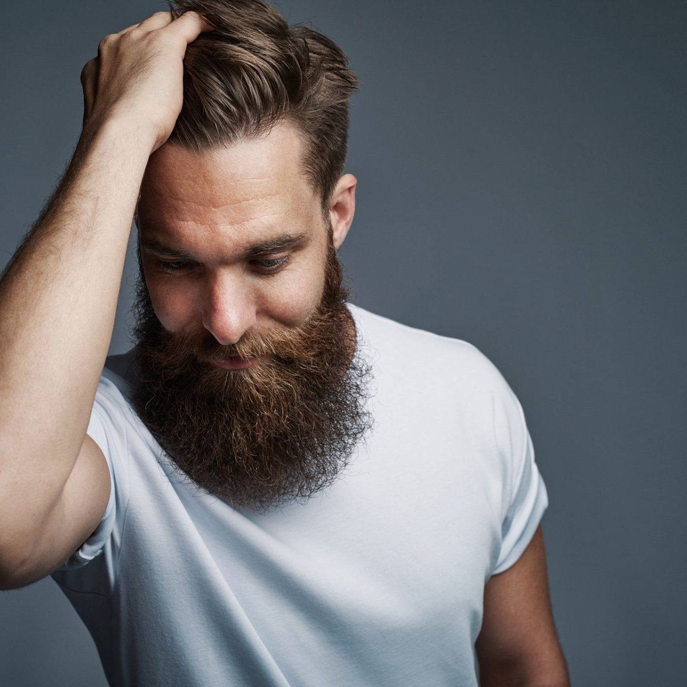 Man with beard running hand through hair